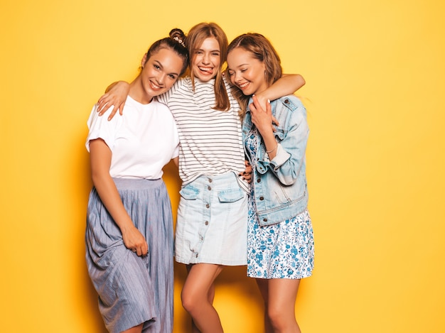 Три молодые красивые улыбающиеся битник девушки в модной летней одежде. сексуальные беззаботные женщины позируют возле желтой стены. веселые позитивные модели