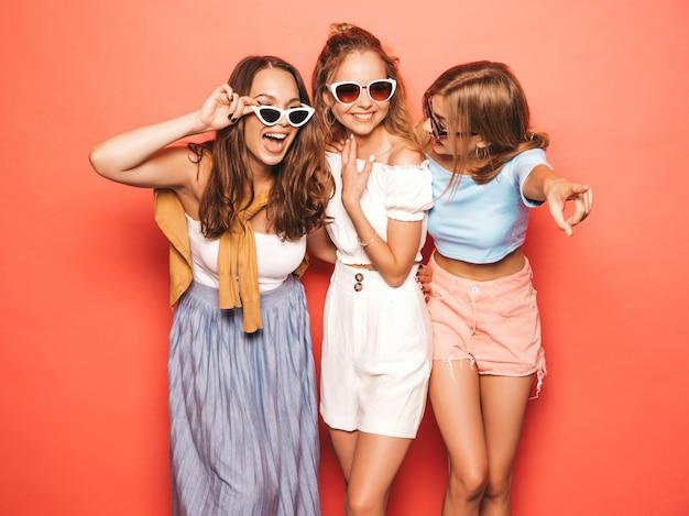 Три молодые красивые улыбающиеся битник девушки в модной летней одежде. сексуальные беззаботные женщины позируют возле желтой стены. позитивные модели веселятся в солнечных очках
