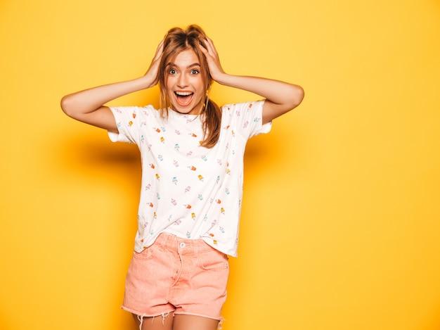 トレンディな夏のジーンズの若い美しい笑顔の内気な少女は服をショートパンツします。女性は黄色の壁に近いポーズします。ショックを受けて驚いた女性の手で頭を握りしめ、悲鳴を上げます。人間の感情