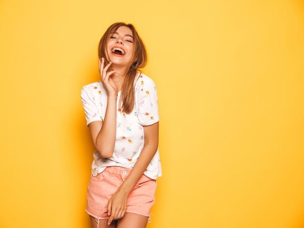 トレンディな夏のジーンズの若い美しい笑顔内気な少女の肖像画は服をショートパンツします。セクシーな屈託のない女性が黄色の壁に近いポーズします。楽しいポジティブモデル
