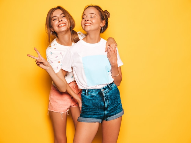Две молодые красивые улыбающиеся битник девушки в модной летней одежде. сексуальные беззаботные женщины позируют возле желтой стены. позитивные модели сходят с ума и веселятся. показывает знак мира