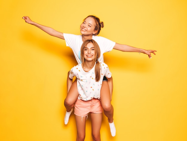 Две молодые красивые улыбающиеся битник девушки в модной летней одежде. сексуальные беззаботные женщины позируют возле желтой стены. модель сидит на спине подруги и поднимает руки