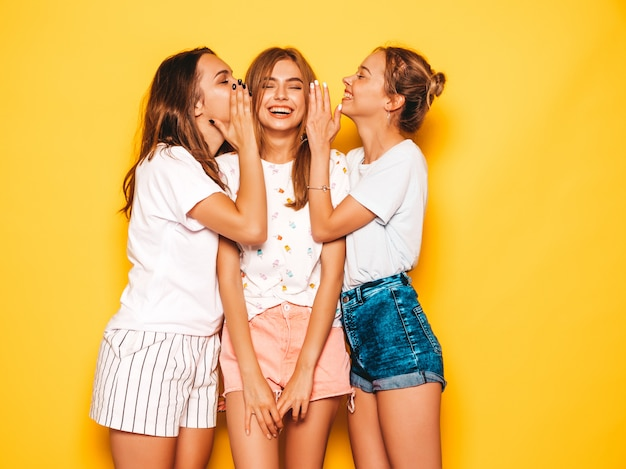 Три молодые красивые улыбающиеся битник девушки в модной летней одежде. сексуальные беззаботные женщины позируют возле желтой стены. позитивные модели сходят с ума и веселятся. делимся секретами, сплетничаем