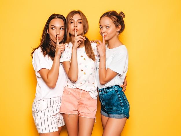 Три молодые красивые улыбающиеся битник девушки в модной летней одежде. сексуальные беззаботные женщины позируют возле желтой стены. позитивные модели сходят с ума. показываю знак молчания палец тишина, жест