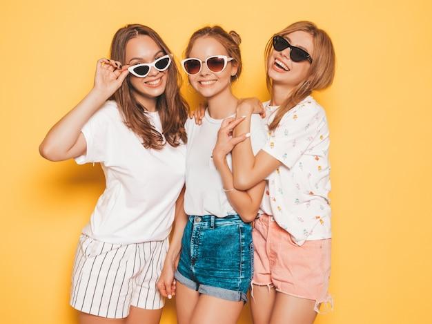 Три молодые красивые улыбающиеся битник девушки в модной летней одежде. сексуальные беззаботные женщины позируют возле желтой стены. позитивные модели сходят с ума и веселятся. делать усы с волосами