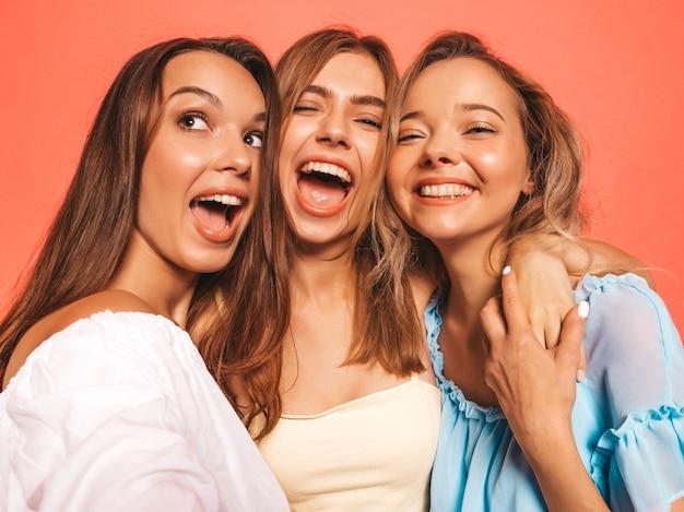 Три молодые красивые улыбающиеся битник девушки в модной летней одежде. сексуальные беззаботные женщины позируют возле розовой стены. позитивные модели сходят с ума. делая селфи автопортрет фотографий на смартфоне