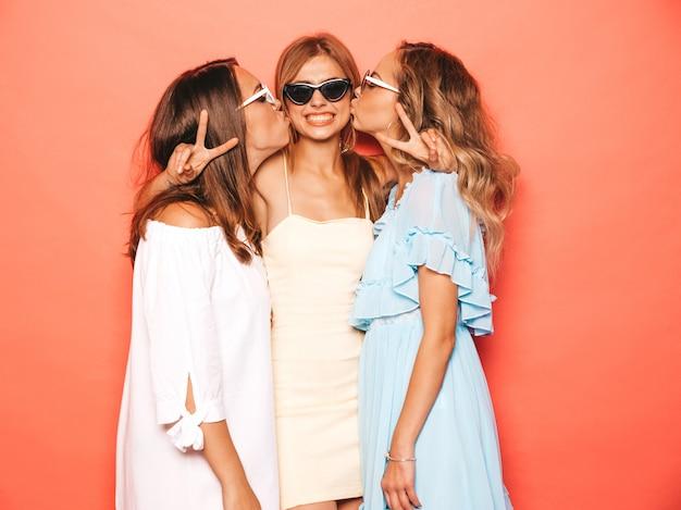 Три молодые красивые улыбающиеся битник девушки в модной летней одежде. сексуальные беззаботные женщины позируют возле розовой стены. позитивные модели сходят с ума и веселятся. целую друга в щеку