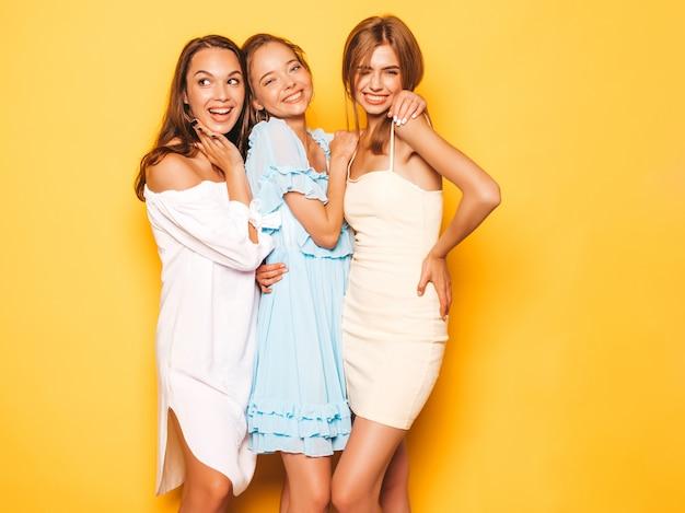Три молодые красивые улыбающиеся битник девушки в модной летней одежде. сексуальные беззаботные женщины позируют возле желтой стены. позитивные модели сходят с ума и веселятся