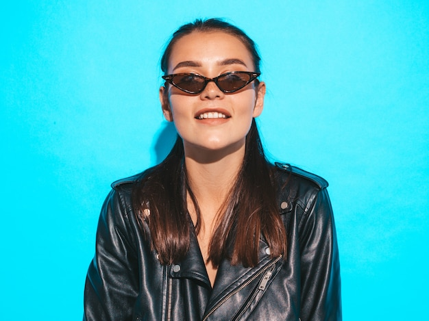 Портрет молодой красивой битник плохая девушка в модной летней черной кожаной куртке и солнцезащитные очки. сексуальная беззаботная женщина, изолированных на синем. брюнетка позирует модель