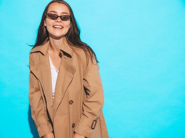 茶色のコートとサングラスで美しい白人ブルネットの女性モデルの肖像画。青い壁に近いポーズの女の子