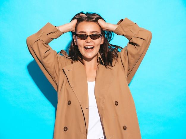 Портрет красивой кавказской модели брюнетка женщина в коричневой шинели и солнцезащитные очки. девушка позирует возле синей стены