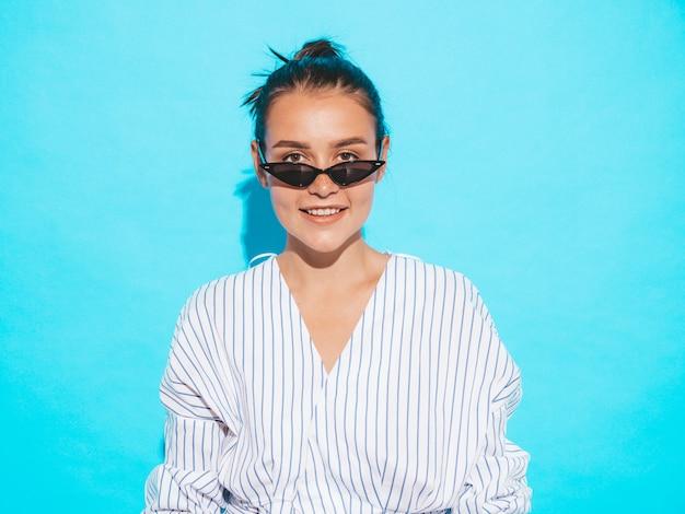トレンディな夏服の若い美しい笑顔内気な少女の肖像画。セクシーな屈託のない女性が青い壁に近いポーズします。サングラスで楽しんでいる肯定的なモデル