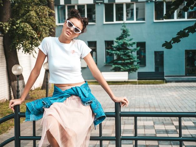 夏の流行に敏感なジャケットジーンズ服に身を包んだ角髪型の美しい笑顔モデル。通りでポーズをとってセクシーな屈託のない少女。サングラスで楽しんでトレンディな面白いと肯定的な女性