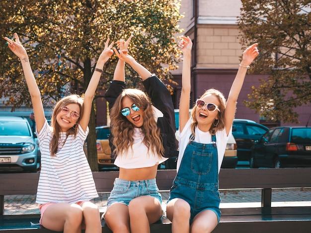 Портрет трех молодых красивых улыбающихся хипстерских девочек в модной летней одежде. сексуальные беззаботные женщины, сидящие на скамье на улице. позитивные модели, весело проводящие время в солнцезащитных очках. поднимая руки