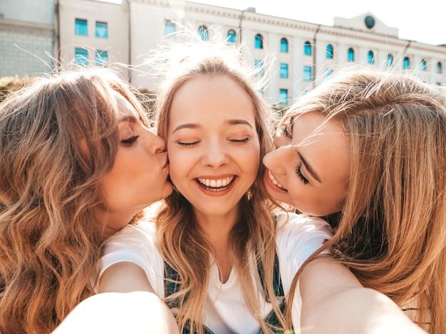 Три молодых улыбающихся хипстерских женщины в летней одежде. девушки, делающие фотографии автопортрета селфи на смартфоне. модели, позирующие на улице. женщины целуют своего друга в щеку