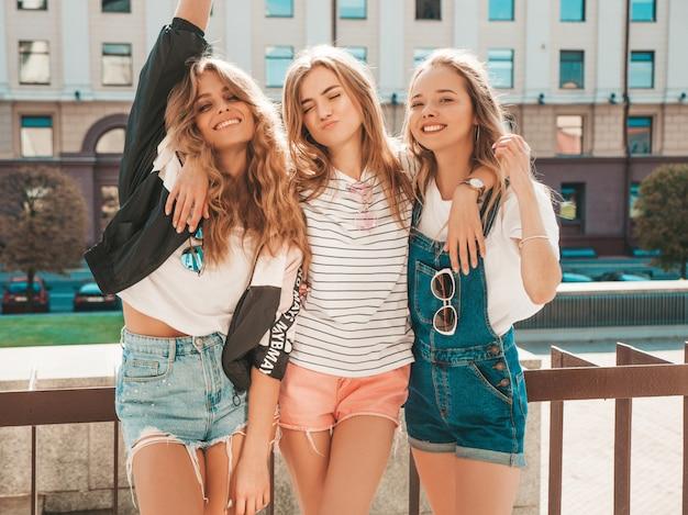 Портрет трех молодых красивых улыбающихся хипстерских девочек в модной летней одежде. сексуальные беззаботные женщины позируют на улице. позитивные модели веселятся. они поднимают руки