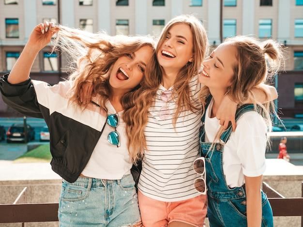 Портрет трех молодых красивых улыбающихся хипстерских девочек в модной летней одежде. сексуальные беззаботные женщины позируют на улице. позитивные модели с удовольствием. обниматься