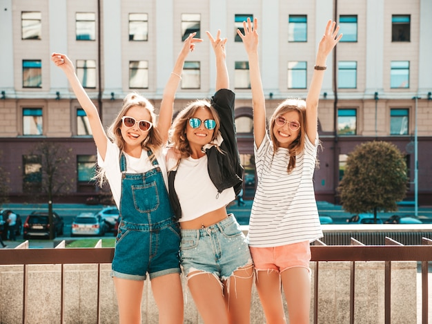 Портрет трех молодых красивых улыбающихся хипстерских девочек в модной летней одежде. сексуальные беззаботные женщины позируют на улице. позитивные модели веселятся в солнечных очках. поднимают руки