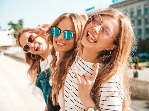 Портрет трех молодых красивых улыбающихся хипстерских девочек в модной летней одежде. сексуальные беззаботные женщины позируют на улице. позитивные модели веселятся в солнечных очках. обнимаются