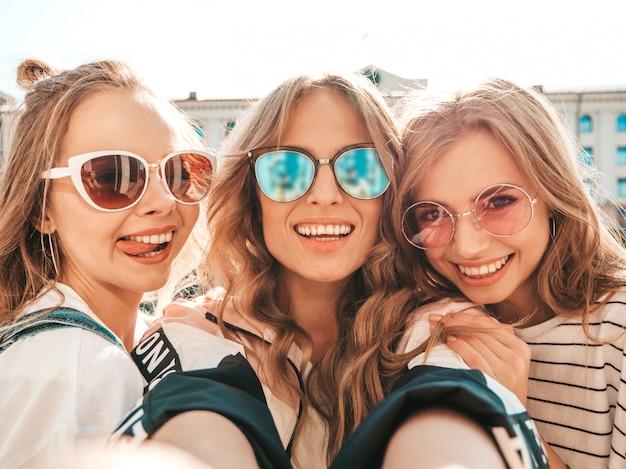 Три молодые улыбающиеся битник женщины в летней одежде. девушки, делающие фотографии автопортрета селфи на смартфоне. модели, позирующие на улице. женщина, показывающая положительные эмоции лица в солнцезащитных очках