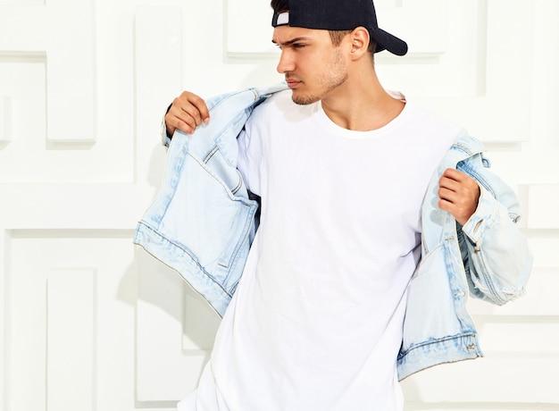 Портрет красивого молодого модельного человека, одетого в джинсовую одежду, позирует возле белой фактурной стены
