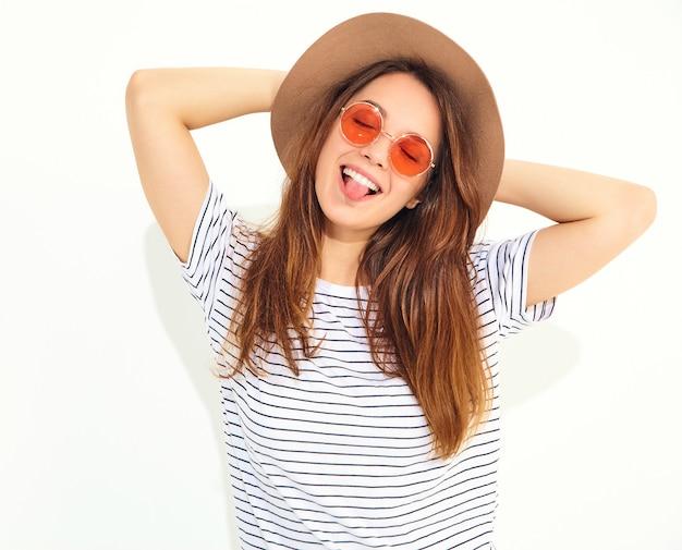 白い壁に分離された自然なメイクと茶色の帽子でカジュアルな夏服の若いスタイリッシュな笑う女性モデルの肖像画。