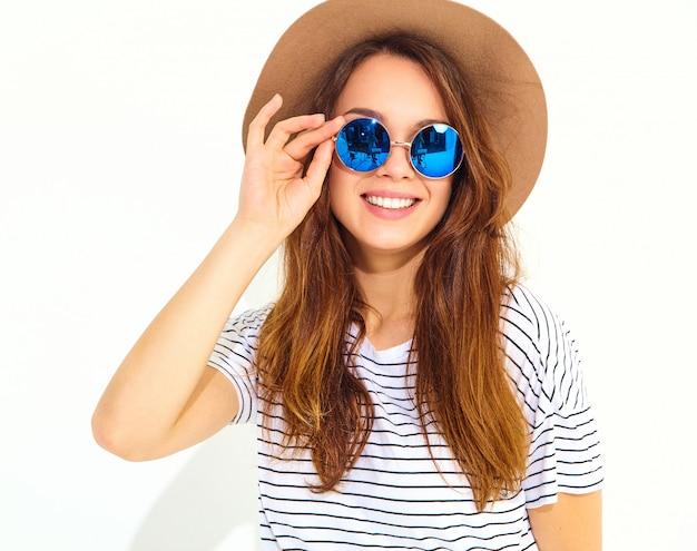 白い壁に分離された茶色の帽子でカジュアルな夏服の若いスタイリッシュな笑う女性モデルの肖像画