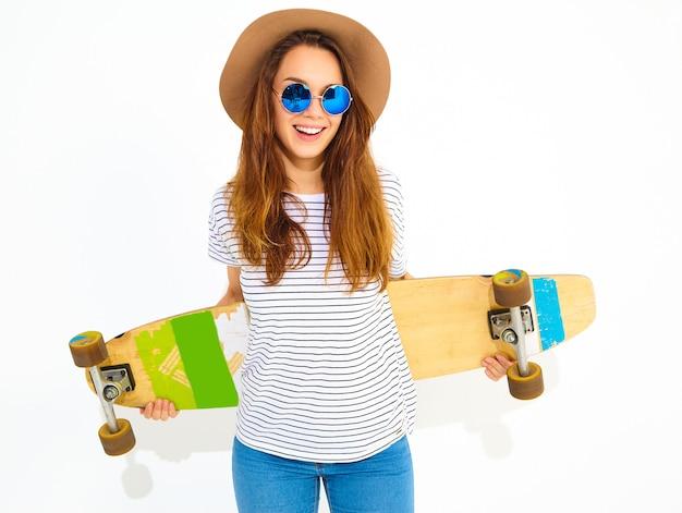 ロングボードデスクでポーズをとって茶色の帽子でカジュアルな夏服の若いスタイリッシュな女性モデルの肖像画。白で隔離