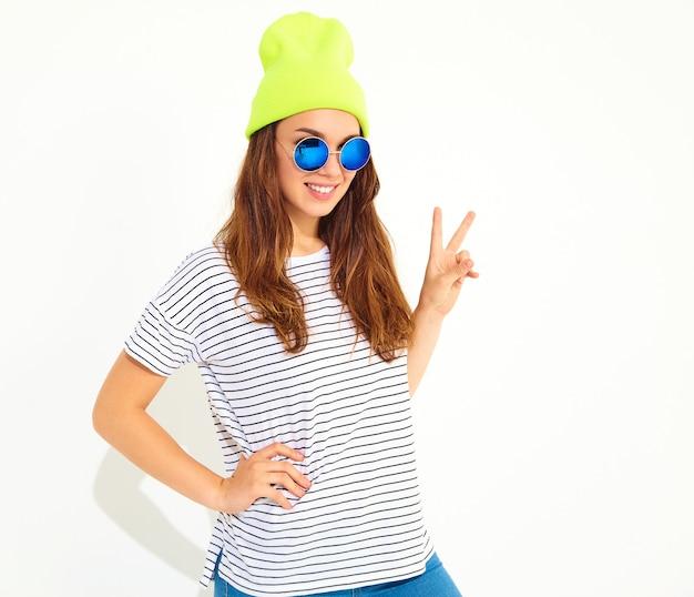 黄色いビーニーハットのカジュアルな夏服の若いスタイリッシュな女性モデルの肖像画。白で隔離