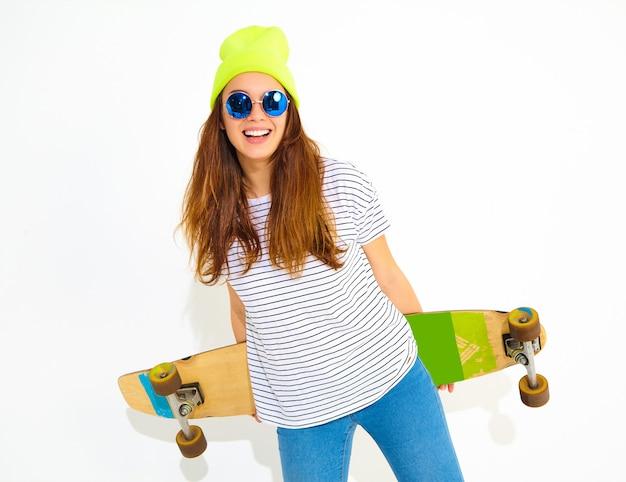 ロングボードデスクでポーズをとって黄色のビーニー帽子でカジュアルな夏服の若いスタイリッシュな女性モデルの肖像画。白で隔離