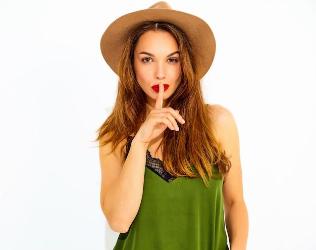 カジュアルな夏の緑服と分離された指で沈黙ジェスチャーを示す赤い唇と茶色の帽子の若いスタイリッシュな女性モデル