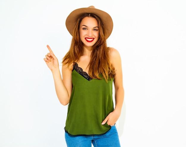 カジュアルな夏の緑の服と赤い唇と茶色の帽子の若いスタイリッシュな女性モデルはアイデアを得て、彼女は彼女の指を上げた。孤立した