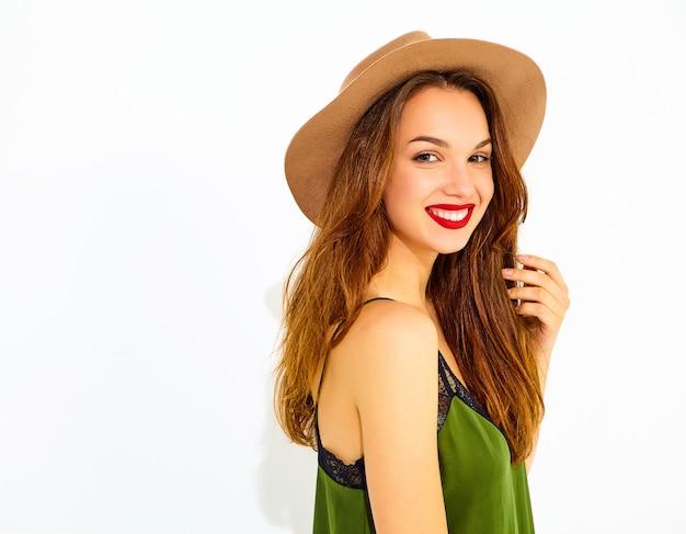 Молодая стильная модель женщины в непринужденной летней зеленой одежде и коричневой шляпе с красными губами, позирующей возле белой стены