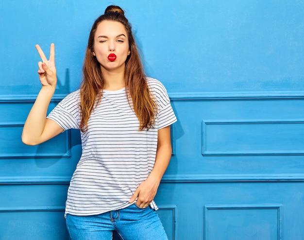 青い壁に近いポーズ、赤い唇とカジュアルな夏服の若いスタイリッシュな女性モデル。キスとピースサインを与える