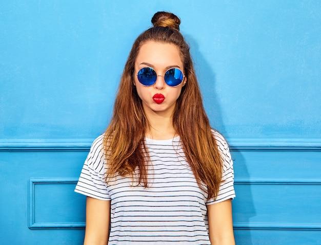 Модель молодой стильной женщины в повседневной летней одежде с красными губами, позирует возле синей стены. пухнуть щеками