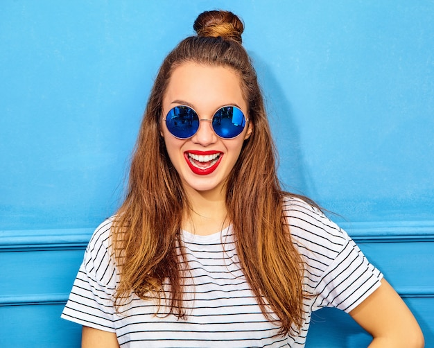 Молодая стильная модель женщины в повседневной летней одежде с красными губами, позирует возле синей стены