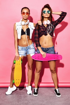 Две молодые стильные улыбающиеся брюнетки с копеечными скейтбордами. модели в летней хипстерской одежде позирует возле розовой стены в студии в темных очках с наушниками