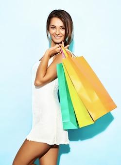 Портрет красивые улыбающиеся шопоголика женщина, держащая красочные бумажные мешки. брюнетка женщина позирует на синей стене после покупок. позитивная модель