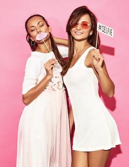 Две смешные улыбающиеся женщины с большими губами и селфи на палочке. смарт и красота концепции. радостные сексуальные молодые модели готовы к вечеринке. горячие женщины изолированные на розовой стене. положительная женщина
