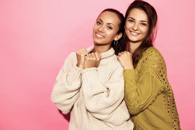 Две красивые улыбающиеся великолепные женщины. женщины стояли в стильных белых и зеленых свитерах, на розовой стене.