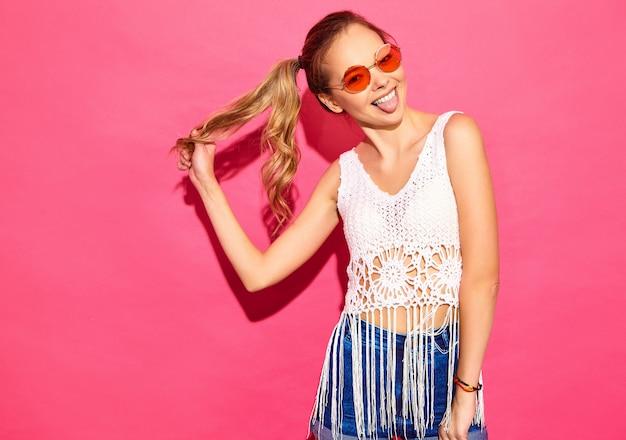 若い美しい女性。彼女の舌を見せてカジュアルな夏服のトレンディな女性。肯定的な女性の感情表情ボディランゲージ。ピンクの壁に分離された面白いモデル