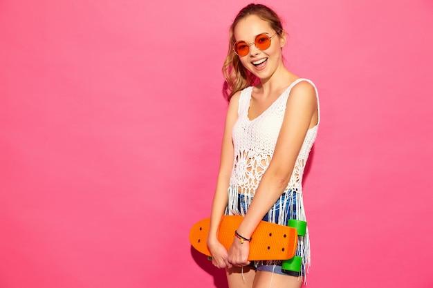 Портрет молодых стильных улыбающихся белокурых женщин с пенни скейтборд. женщины летом белое платье позирует возле розовой стены