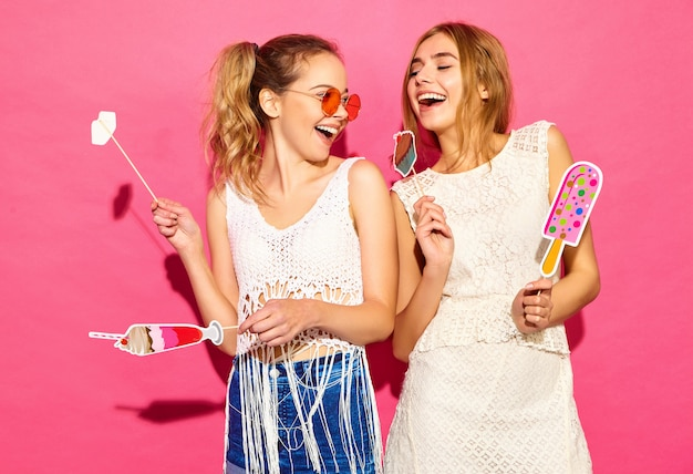 Две молодые стильные улыбающиеся белокурые женщины едят реквизит, сладкое мороженое и фальшивый коктейль. позитивные модели в летней хипстерской одежде позируют возле розовой стены в солнечных очках