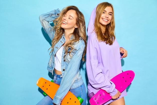 Две молодые стильные улыбающиеся белокурые женщины с пенни скейтбордами. женщины в летней спортивной одежде битник позирует возле синей стены. позитивные модели