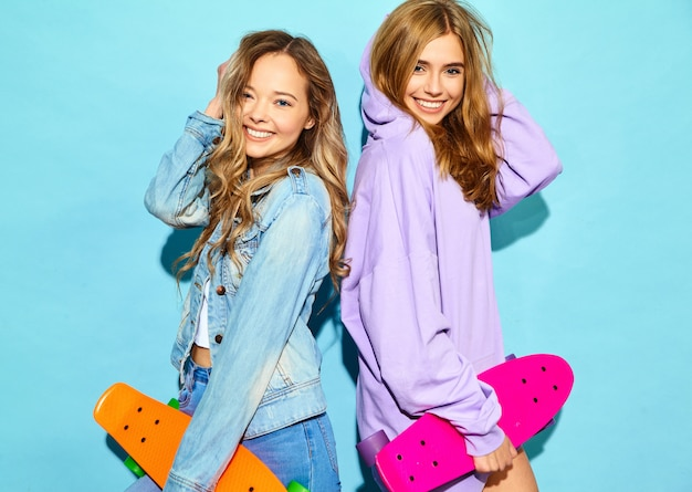 Две молодые стильные улыбающиеся белокурые женщины с пенни скейтбордами. модели в летних битник спортивной одежды позирует возле синей стены. положительная женщина