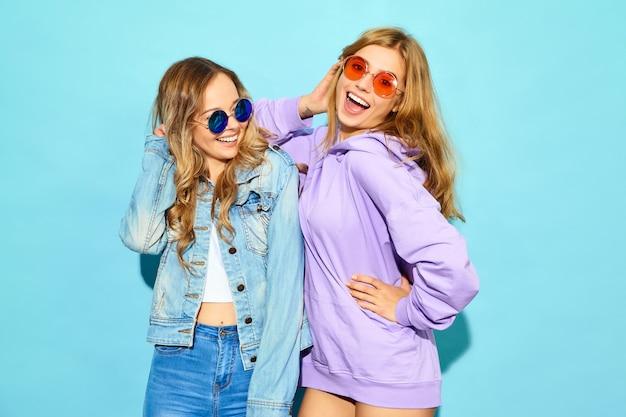 Две молодые красивые белокурые улыбающиеся женщины битник в модной летней одежды. сексуальные беззаботные женщины позируют возле синей стене в солнцезащитные очки. позитивные модели сходят с ума