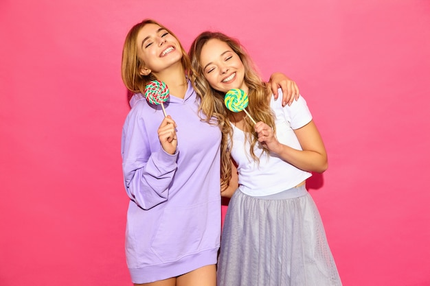Две молодые красивые улыбающиеся блондинка битник женщины в модной летней одежды. беззаботные горячие женщины позируют возле розовой стены. позитивные прикольные модели с леденцом на палочке