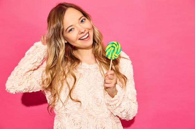 トレンディな夏服の若い美しい笑顔流行に敏感な女性。セクシーな屈託のない女性がピンクの壁に近いポーズします。ロリポップを食べるポジティブモデル