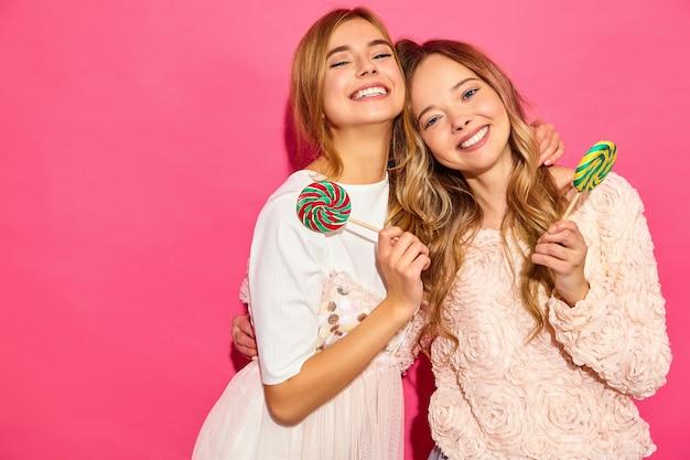 Две молодые красивые улыбающиеся блондинка битник женщины в модной летней одежды. беззаботные горячие женщины позируют возле розовой стены. позитивные смешные модели обнимаются с леденцом