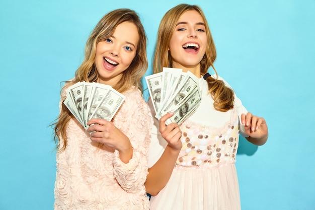 Портрет двух счастливых восторженных белокурых женщин, носящих летнюю одежду, радуясь победе и держа наличные деньги изолированными над синей стеной
